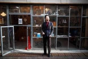 shuhei okawara con una delle sue maschere di fronte al suo negozio, kamenya omore